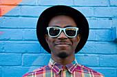 Black man wearing sunglasses near colorful wall
