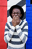 Black man laughing near colorful wall