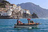 Fisherman in fishing boat heads out to sea from Amalfi harbour, with view towards Amalfi town, Costiera Amalfitana (Amalfi Coast), UNESCO World Heritage Site, Campania, Italy, Europe
