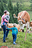 Family, mother and two children standing in front of an alpine meadow, cows with cowbell, MR, Maria Alm, Berchtesgadener Land, Alps, Austria, Europe