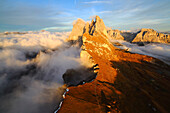 Aerial shot from Seceda of Odle surrounded by clouds at sunset in the Dolomites, Val Funes, Trentino Alto-Adige South Tyrol, Italy, Europe