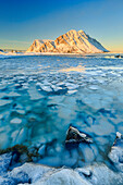 Views of the mountains of Gymsoya (Gimsoya) from Smorten reflected in the clear sea still partially frozen, Lofoten Islands, Arctic, Norway, Scandinavia, Europe