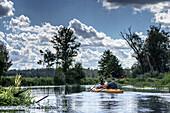 Touristen-Pärchen in einem gelben Zwei-Mann-Kajak paddeln auf einem Flussarm im Unterspreewald bei Sonnenschein und lockerer Bewölkung, vom Kajak aus fotografiert, Biosphärenreservat, Schlepzig, Brandenburg, Deutschland