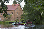 Kayak tourists paddling through a village and passing by a brick house, biosphere reserve, Schlepzig, Brandenburg, Germany