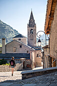 Young Adult Woman Walking Through Quaint Village, Rear View, Lanslevillard, Val Cenis Vanoise, France