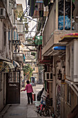 Chinese woman leaves her house in narrow streets of Cheng Chau Island, Hongkong, China, Asia