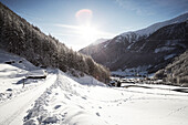 snowy road in winter landscape and village, Unser Frau, Schnalstal, South Tirol, Italy