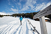 Person snow shoeing in front of signpost, Kreuzwiesenalm, Luesen, South Tyrol, Italy
