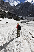 Woman hiking in the snow in front of the north face of Mount Triglav, highest peak in Slovenia, Vrata Valley, Triglav National Park, Julian Alps, Slovenia, Europe