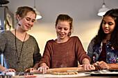 11 years old girls baking christmas cookies, kneading dough, Hamburg, Germany