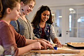 11 years old girls baking christmas cookies, cutting out dough, Hamburg, Germany