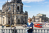 Female tourist with city map, guide book, view from Bruehl's Terrace towards Dresden cathedral, Catholic Court Church and Semper Opera House, MR, Dresden, Saxony, Germany, Europe