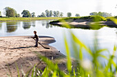 Boy playing near the river, Family bicycle tour along the river Elbe, adventure, from Torgau to Riesa, Saxony, Germany, Europe