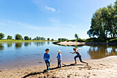 Children thropwing stone, Family bicycle tour along the river Elbe, adventure, from Torgau to Riesa, Saxony, Germany, Europe