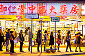 People queuing at a bus stop, evening, pharmacy, shopping street, advertisements, street scene, shopping area Causeway Bay, Hong Kong, China, Asia