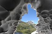 View from a snow cave to Gargglerin, Stubai Alps, Tyrol, Austria