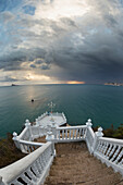Steps leading down to the turquoise water with the sun glowing on the horizon under storm clouds, Benidorm, Spain
