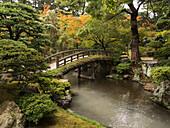 Japanese stone bridge across a stream in a park, Kyoto, Japan