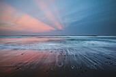Amazing sunset rays of light over ocean horizon, Black sand beach at Pololu Valley, North Kohala, Island of Hawaii, Hawaii, United States of America