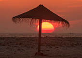 Silhouette of a beach umbrella on the beach with a colourful sun sinking into the horizon over the ocean, Tarifa, Cadiz, Andalusia, Spain