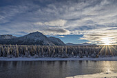 The sun breaks through the clouds above the Takhini River on a late winter afternoon, near Whitehorse, Yukon, Canada