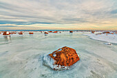 Sunset lights up the rocks and ice covered Hudson Bay, Manitoba, Canada
