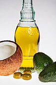 Close up of a coconut, olives, avocados, and glass bottle of olive oil on a white background, Calgary, Alberta, Canada