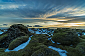 The sun sets over a moss covered lava flow along the south coast of Iceland, Iceland