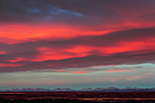 Dramatic colourful sky at sunrise with mountain range in the distance, Calgary, Alberta, Canada