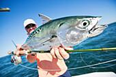 Fisherman holds a fresh caught false albacore, Cape Cod, Massachusetts, United States of America