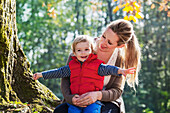 A mother holding her toddler son in a park in autumn, Langley, British Columbia, Canada