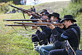 A line of American Civil War union re-enactors on the battlefield with guns in the firing position, United States of America