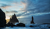 Large waves crash against the rocks and southern shoreline near Vik, Iceland