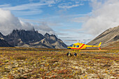 Three men get out of a helicopter on a mountain top in Tombstone Territorial Park, Yukon, Canada