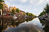 'Tranquil water reflecting buildings and trees in a canal, Singelgracht; Amsterdam, Netherlands'