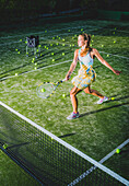 A girl on a tennis court with a racquet and numerous tennis balls, Tarifa, Cadiz, Andalusia, Spain