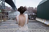 Woman in low-back dress walking in industrial area