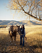 Woman leading horse on dirt path