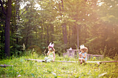 Girls playing telephone on wooden log in garden