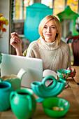 Caucasian entrepreneur using laptop in shop