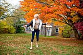Caucasian woman jumping for joy in backyard
