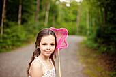 Caucasian girl carrying butterfly net on dirt road