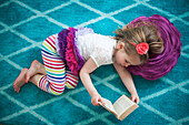 Girl reading book on floor