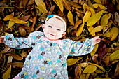 Mixed race baby girl laying in autumn leaves
