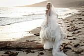 Caucasian bride walking on beach