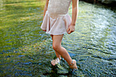 Girl standing barefoot in pond