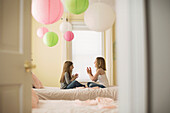 Caucasian girls playing clapping game in bedroom