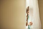 Shy Caucasian girl peeking around curtain