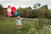 Caucasian girl carrying balloons in rural field