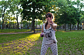Caucasian woman gesturing peace sign in park